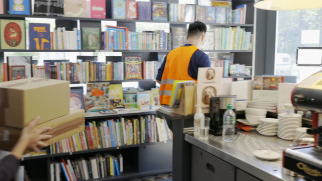 courier man doing a delivery at bookstore during covid-19 pandemic - book shop stock videos & royalty-free footage