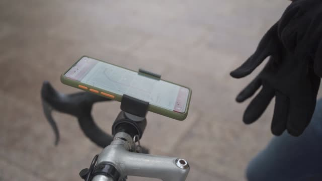 courier on a bike looking at directions on gps on his mobile app so he can find right address to deliver - direction stock videos & royalty-free footage