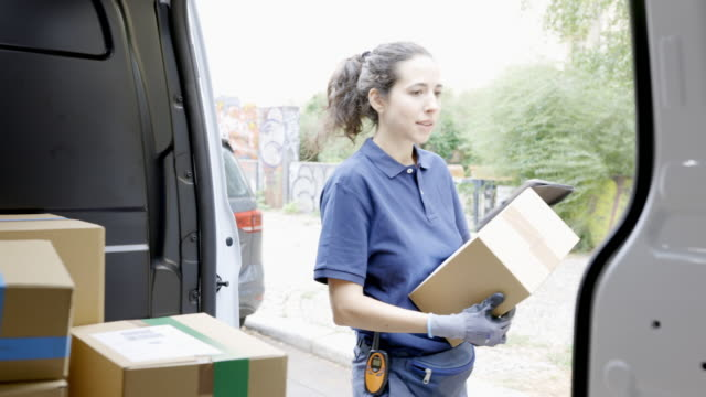 courier person goes on delivering a parcel - unloading stock videos & royalty-free footage