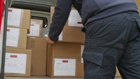 courier stacking the packages onto the cart - unloading stock videos & royalty-free footage