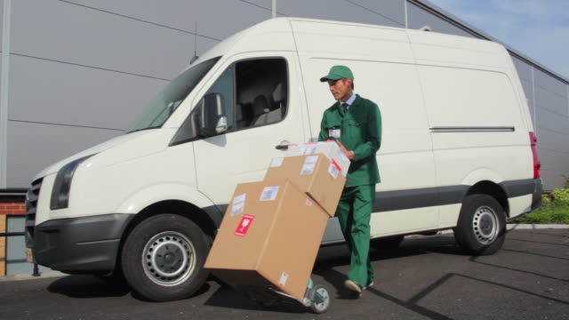 vídeos de stock, filmes e b-roll de ms pan courier wearing uniform delivering cardboard packages to warehouse / london, united kingdom - entregador