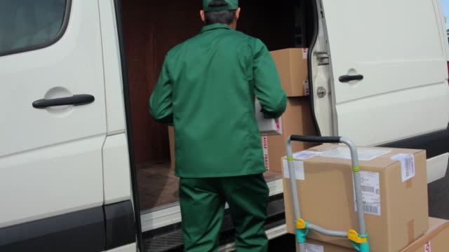 MS Courier wearing uniform loading packages into van from hand truck / London, United Kingdom