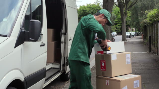 ms courier wearing uniform scanning packages with bar code reader standing outside van on street. man smiling at camera / london, united kingdom - delivery person stock videos & royalty-free footage