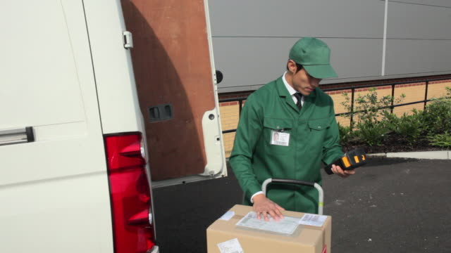 ms ha courier wearing uniform unloading and scanning packages with bar code reader outside warehouse / london, united kingdom - 段ボール箱点の映像素材/bロール