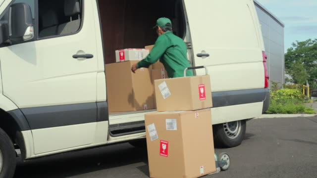 vídeos de stock, filmes e b-roll de ms courier wearing uniform unloading packages from van onto hand truck / london, united kingdom - entregador