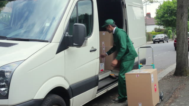 ms courier wearing uniform unloading packages from van onto hand truck on street / london, united kingdom - 積荷を降ろす点の映像素材/bロール