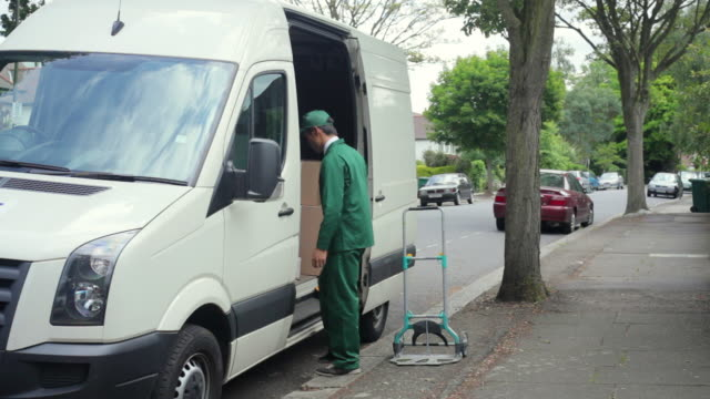 ws courier wearing uniform unloading packages from van onto hand truck on street / london, united kingdom - carrying stock-videos und b-roll-filmmaterial