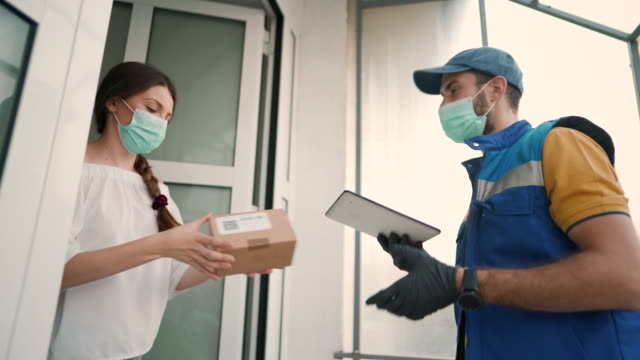 courier with protective face mask delivering package to a client - confezione video stock e b–roll