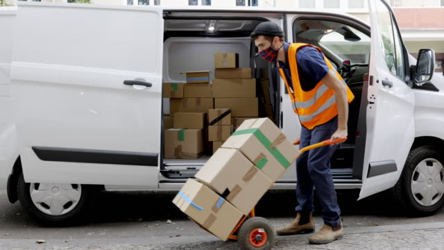 courier worker moving cardboard boxes on a cart - van stock videos & royalty-free footage