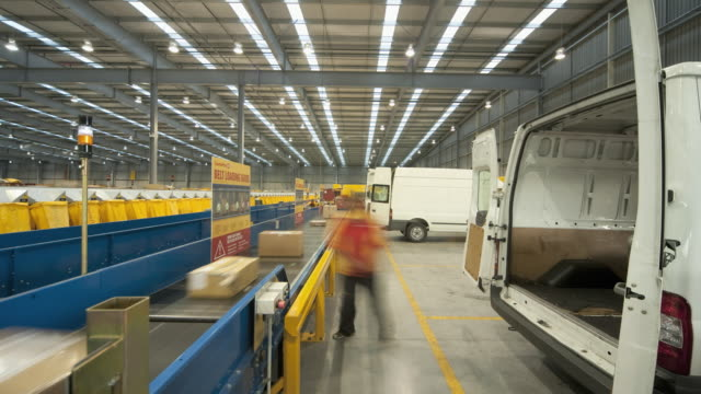 vídeos y material grabado en eventos de stock de t/l ws couriers loading parcels out of vans onto ingestion conveyer, auckland, new zealand - toma ancha