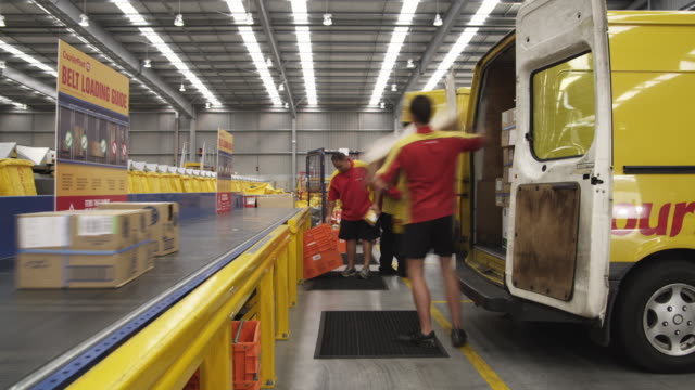 vídeos de stock, filmes e b-roll de t/l ws couriers loading parcels out of vans onto ingestion conveyer, auckland, new zealand - entregador