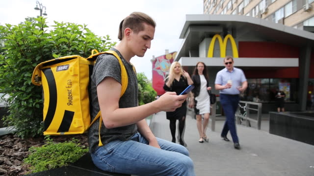 couriers of yandex.eda service at work in moscow, russia, on thursday, may 30, 2019. yandex.eda is a service that allows you to order food from your... - fast food stock-videos und b-roll-filmmaterial