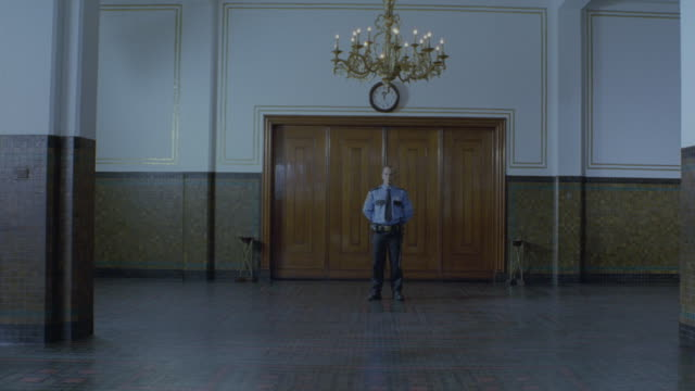 a court security officer standing guard in front of courtroom. - wachmann stock-videos und b-roll-filmmaterial