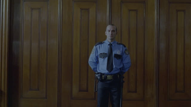 A Court security officer standing guard in front of courtroom.