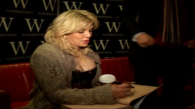 Courtney Love book signing and interview Vars Courtney Love sits on sofa and signs copy of her book for reporter