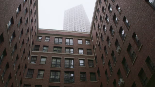 stockvideo's en b-roll-footage met ws courtyard highrise apartments on overcast day - baksteen