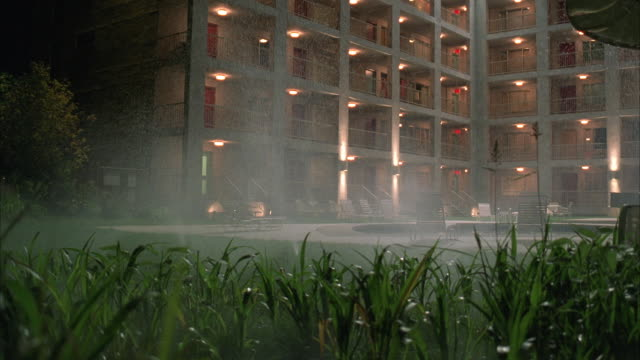 ms ds courtyard of large story apartment building complex, lawn sprinklers pop in foreground - sprinkler stock videos & royalty-free footage