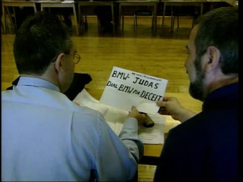 vídeos y material grabado en eventos de stock de coventry men at rover meeting looking at sheet of paper with 'bmw judas dial bmw for deceit' written on rover worker at meeting men at meeting - judas