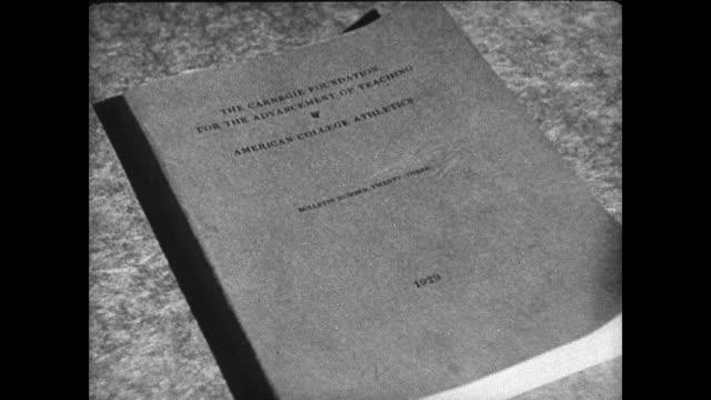 cover of 1929 report from carnegie foundation page of report on 'recruiting amp subsidizing' reprising men socializing in club man saying they're... - 1936 bildbanksvideor och videomaterial från bakom kulisserna