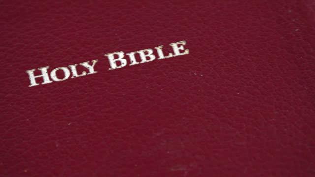 vidéos et rushes de cover of a holy bible turning on display - couverture de livre