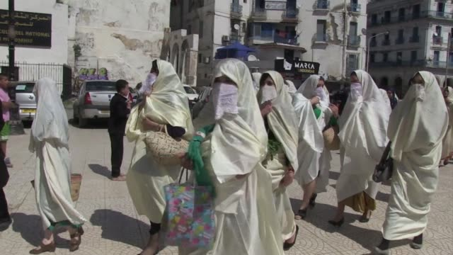covered from head to toe in white their faces partly masked by embroidered triangular cloths algerian women marched through the capital thursday to... - lappen reinigungsgeräte stock-videos und b-roll-filmmaterial