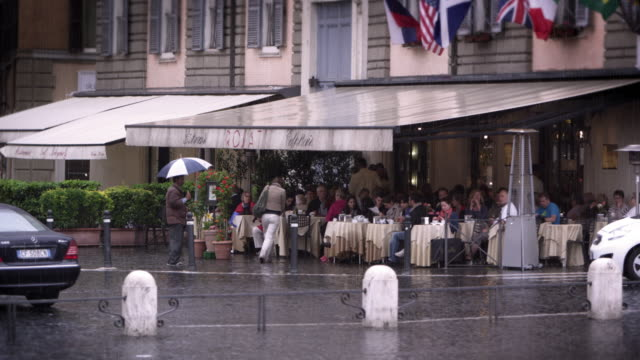 Covered roman cafe filled with people eating