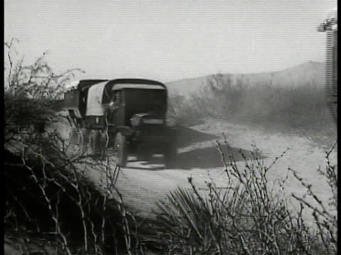covered trucks moving on desert road armoured cars soldiers on motorcycles leaving garage truck towing artillery moving through town mule teams pull... - 1935 stock-videos und b-roll-filmmaterial
