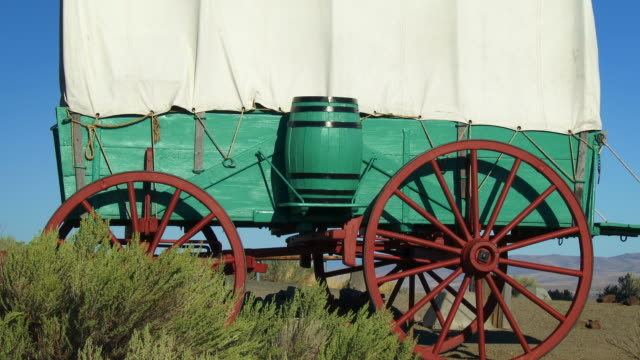 A covered wagon sits on the prairie along the Oregon Trail