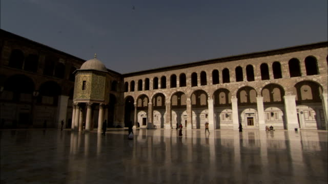 A covered walkway surrounds the courtyard of the Umayyad Mosque Damascus. Available in HD.