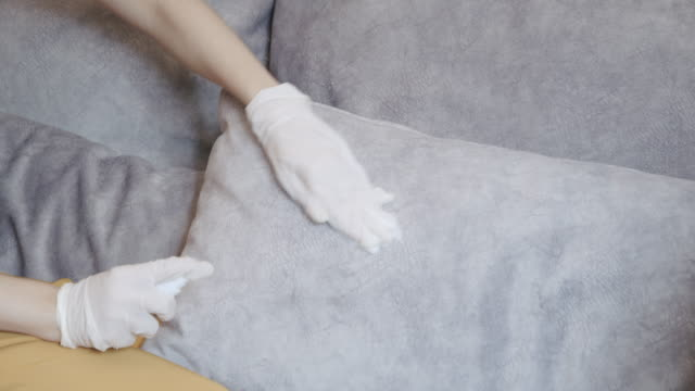 covid 19 situation asian woman hands wearing a glove and disinfection wipes, alcohol and antiseptic cleaning her sofa in the living room. lockdown time from coronavirus. - surface level stock videos & royalty-free footage