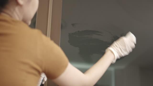 situazione covid 19 le mani delle donne asiatiche che indossano un guanto e salviette di disinfezione, vetro della casa per la pulizia alcolica e antisettica, finestra nel soggiorno. tempo di blocco dal coronavirus. - pulire video stock e b–roll