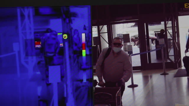 vídeos y material grabado en eventos de stock de covid19 precaution signage is displayed as passengers walk past thermal imaging cameras at los angeles international airport thermal cameras screen... - escritura occidental
