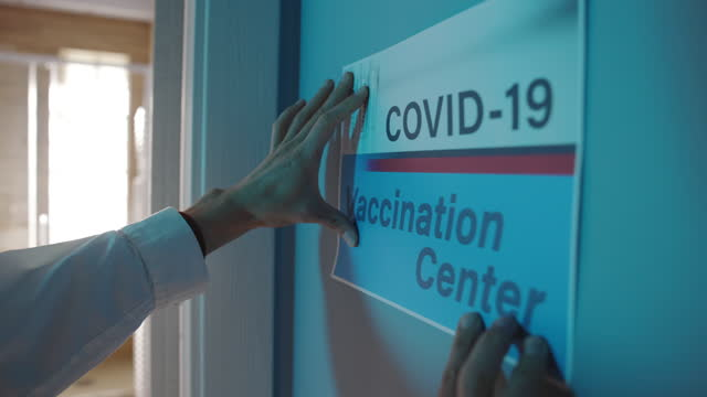 covid-19 vaccination center opening - one mid adult woman only stock videos & royalty-free footage