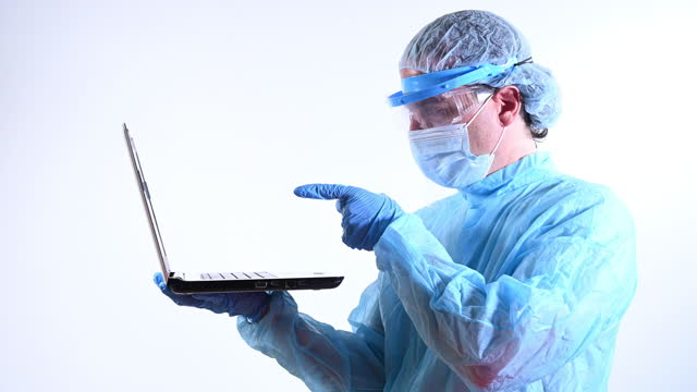 covid-19 vaccine. a scientist pointing out with his index finger to a laptop. he is wearing a protective mask, glasses and a protective suit. - index finger stock videos & royalty-free footage