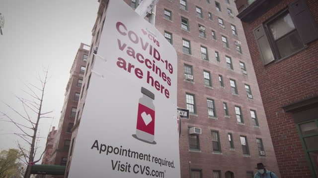 """covid-19 vaccines are here"""" reads a sign in front of a cvs pharmacy on april 04, 2021 in brooklyn new york. - brooklyn new york stock videos & royalty-free footage"""