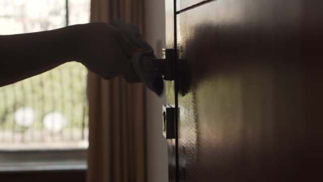 covid-19 wiping down metal handle and door knobs surfaces by an asian man obsessively disinfecting them - portello video stock e b–roll