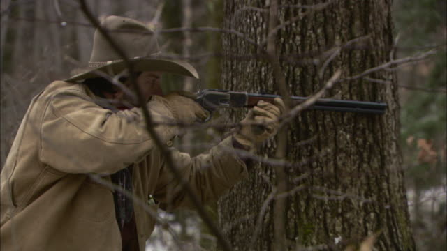 a cowboy aims a rifle in a forest. - hunting stock videos & royalty-free footage
