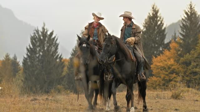 DS Cowboy och cowgirl njuter sin häst rida i naturen