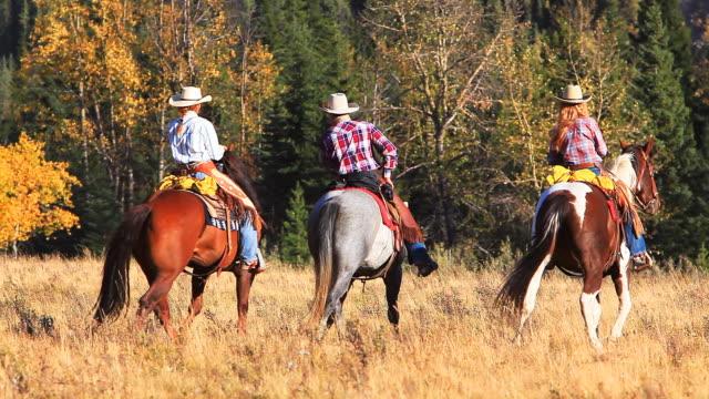 Cowboys und Cowgirls trick Ausritt zu Pferd