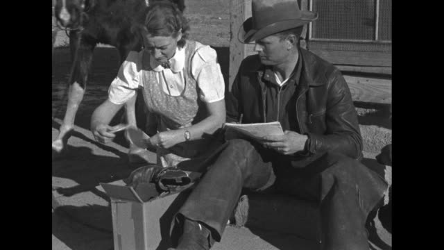 WS cowboy and woman sit on steps to house on prairie packing a box dog cat horse look on / MS same couple arrange boot letters in box / CU box...