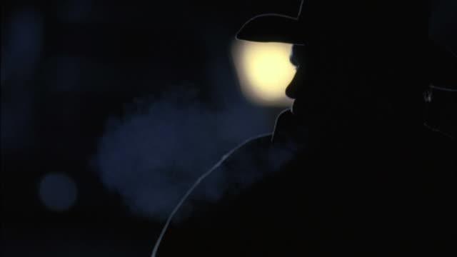 cu cowboy blowing smoke in dark  / tejon ranch, california, usa - 息を吸う点の映像素材/bロール