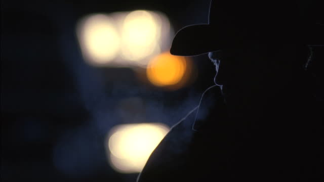 CU Cowboy blowing smoke in dark  / Tejon Ranch, California, USA