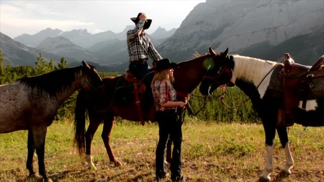 cowboy/ cowgirl exchange kisses on horseback - tiptoe stock videos & royalty-free footage
