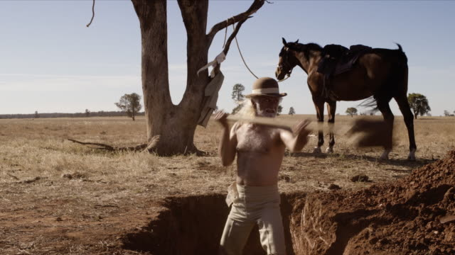 vidéos et rushes de cowboy digging grave, dolly back shot from front - creuser
