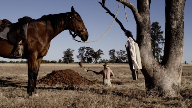 cowboy digging grave, dolly forward shot from behind - steve munro stock videos & royalty-free footage