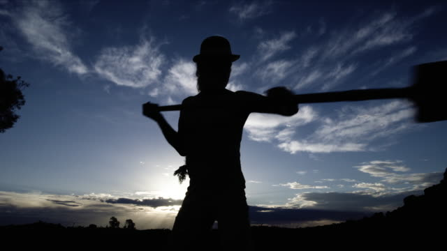 cowboy digging grave in silhouette from grave pov - digging stock videos & royalty-free footage