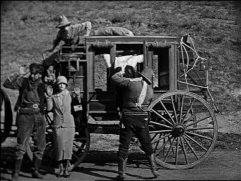 stockvideo's en b-roll-footage met b/w 1924 cowboy dragging man from stagecoach in holdup / feature - 1924