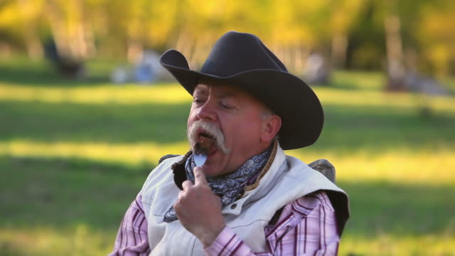 stockvideo's en b-roll-footage met cowboy eating steak dinner - cowboyhoed