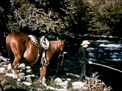 vídeos de stock, filmes e b-roll de 1950 cowboy fishing in river / gunnison, colorado / audio - gunnison