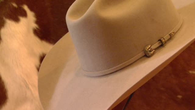 Cowboy hat on display in front on cow hide